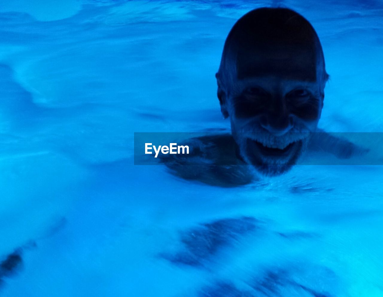 swimming pool, looking at camera, portrait, smiling, water, swimming, one person, blue, happiness, underwater, cheerful, outdoors, one man only, men, mammal, human body part, close-up, day, nature, adult, young adult, people, only men