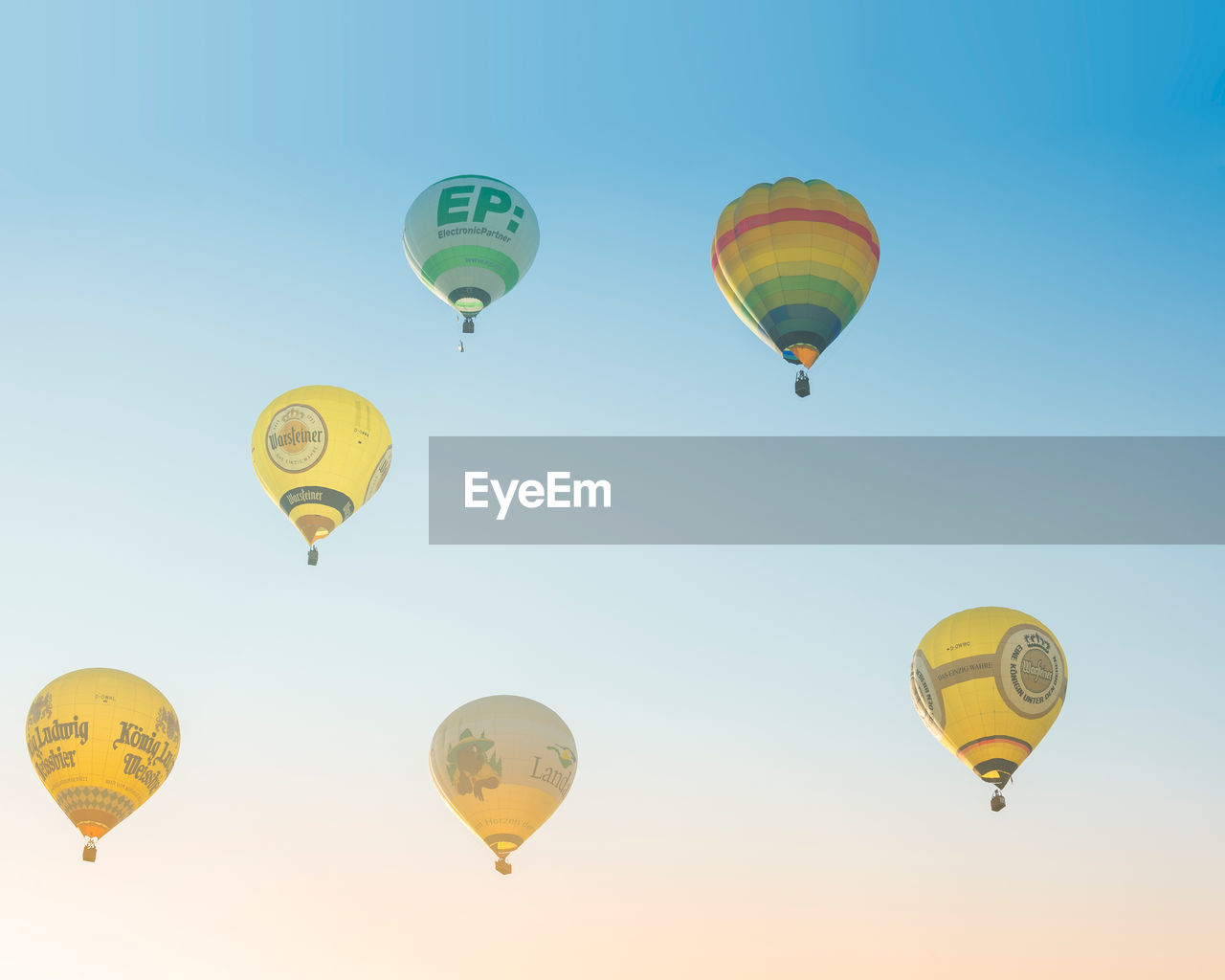 air vehicle, flying, hot air balloon, balloon, transportation, mid-air, sky, multi colored, adventure, nature, low angle view, no people, ballooning festival, clear sky, yellow, travel, extreme sports, group of objects, mode of transportation, outdoors
