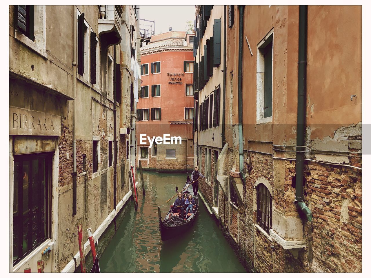 canal, architecture, nautical vessel, building exterior, gondola, built structure, boat, gondola - traditional boat, transportation, real people, day, mode of transport, outdoors, gondolier, wooden post, men, water, oar, rowing, one person, moored, people