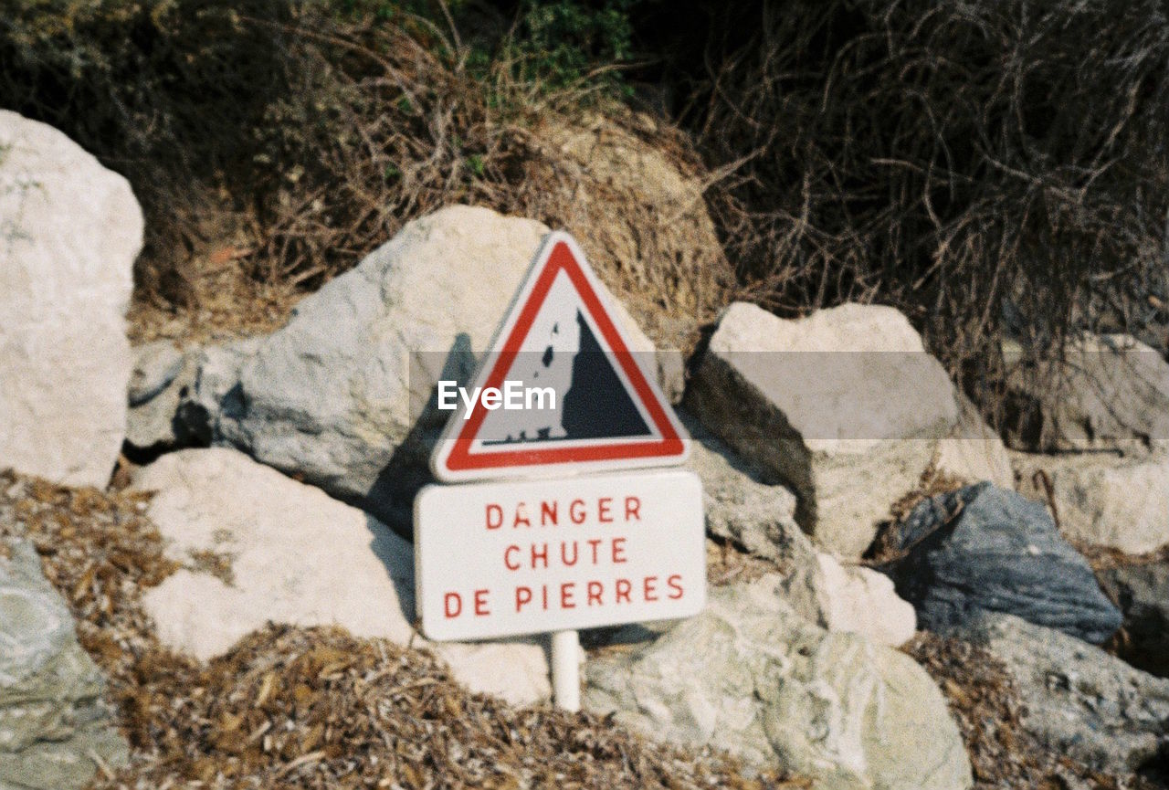 communication, sign, warning sign, solid, rock - object, rock, text, triangle shape, shape, nature, safety, day, no people, road, close-up, outdoors, western script, road sign, guidance, risk, warning symbol