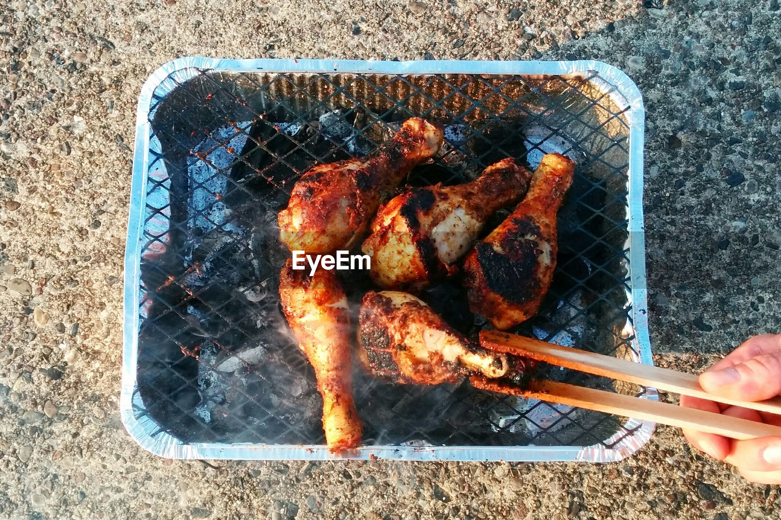 Cropped hand of person grilling meat on metal grate