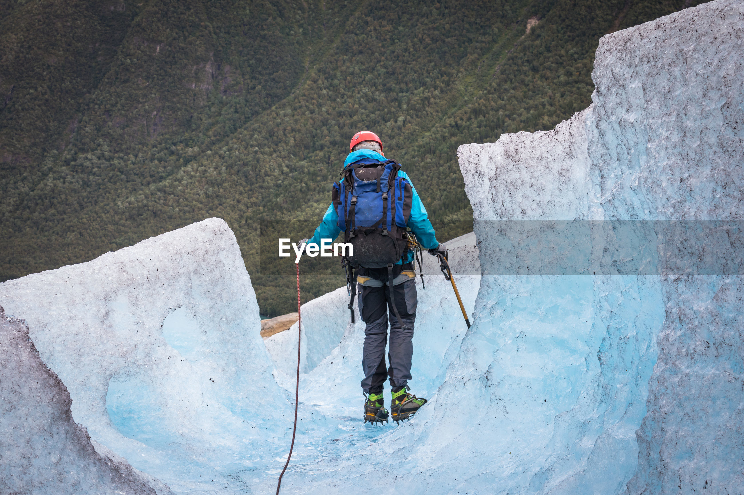 Rear view of hiker on glacier