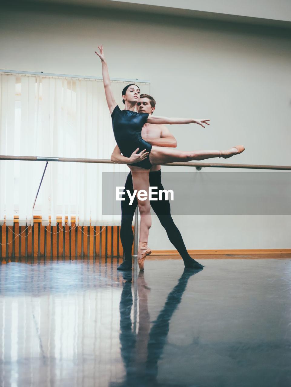 Full Length Of Dancers Dancing In Ballet Studio
