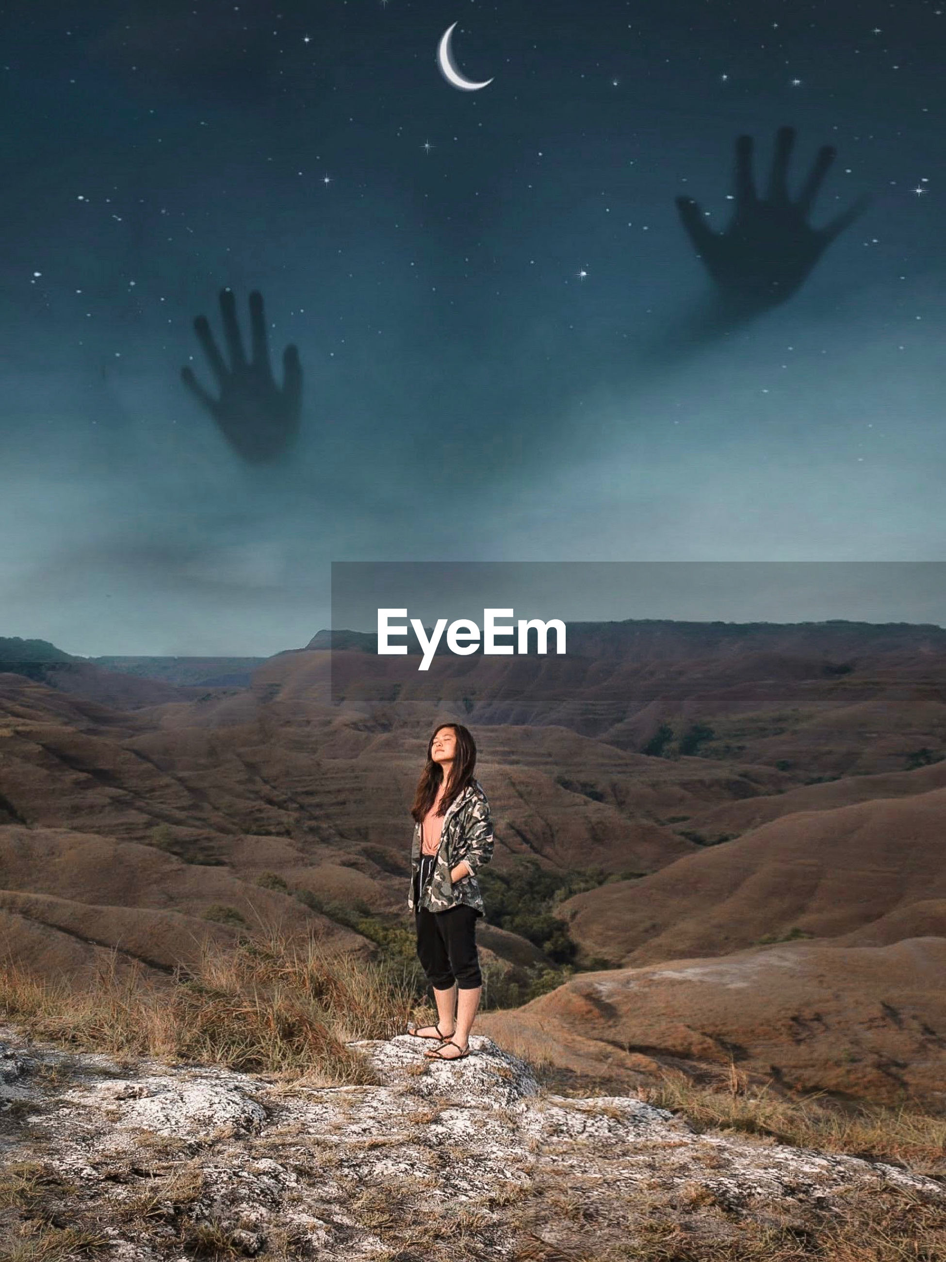 Digital composite image of teenage girl standing on mountain at night