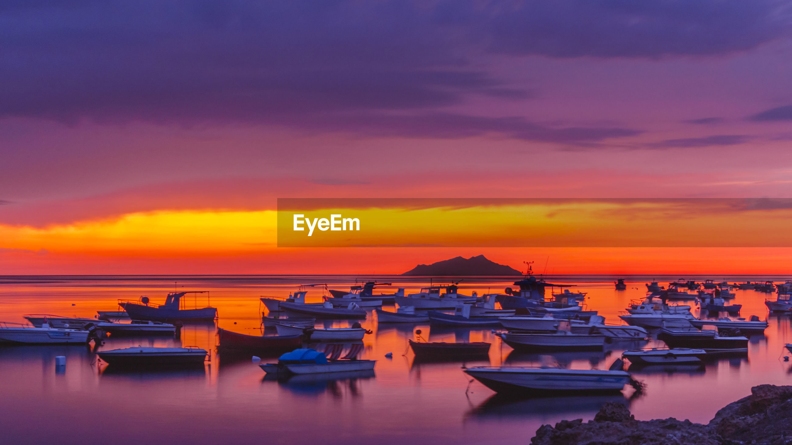 Boats moored in sea against pink sky during sunset
