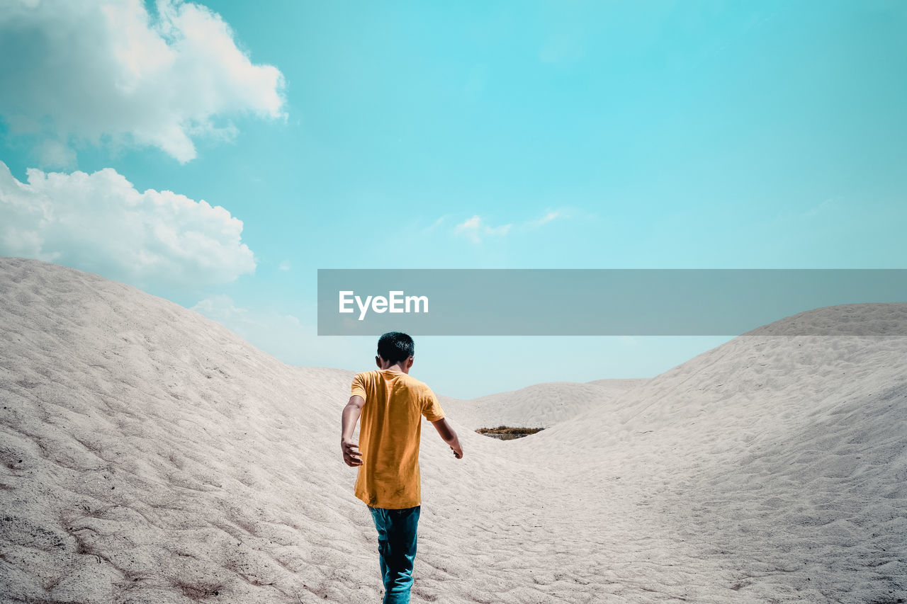 Rear view of boy walking at desert against blue sky