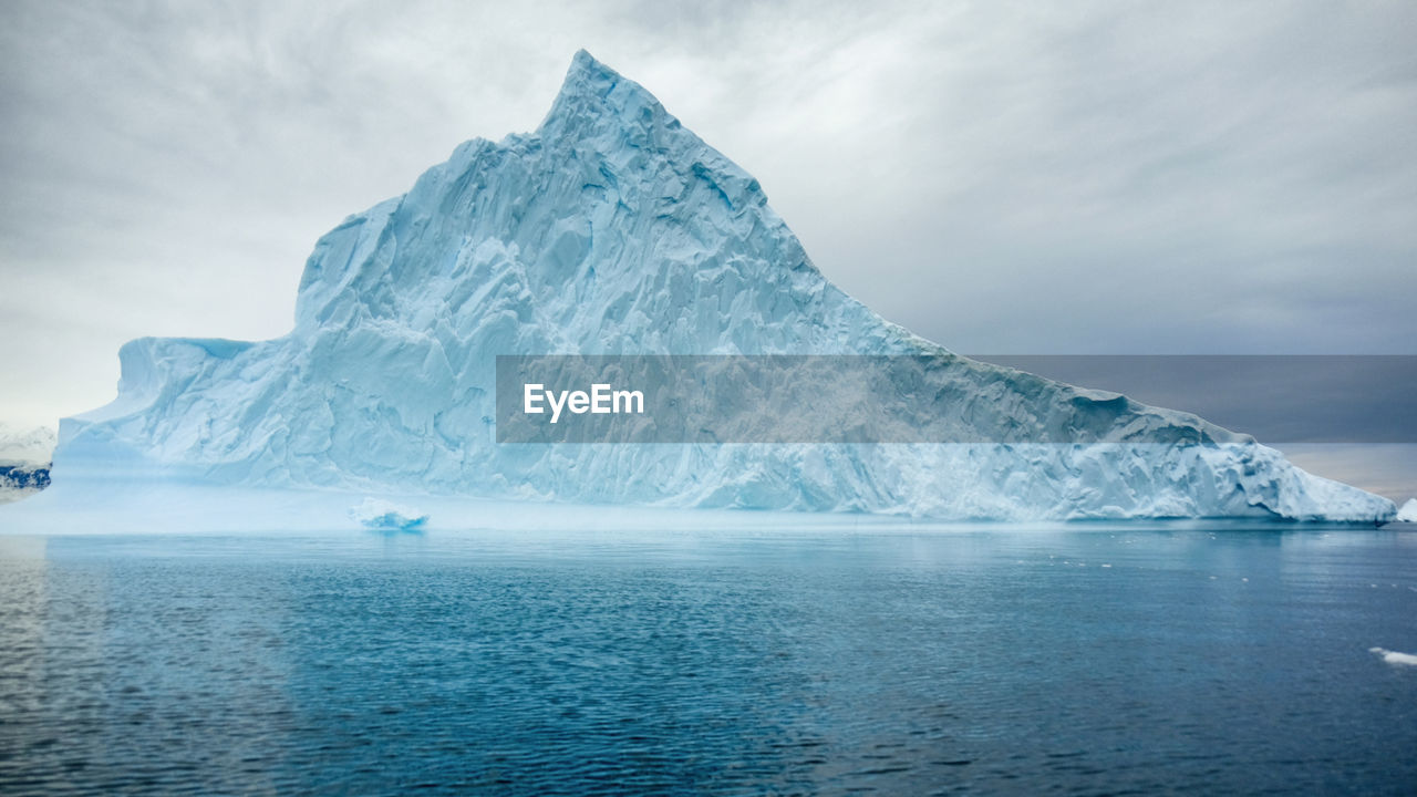 Scenic View Of Iceberg In Sea Against Sky