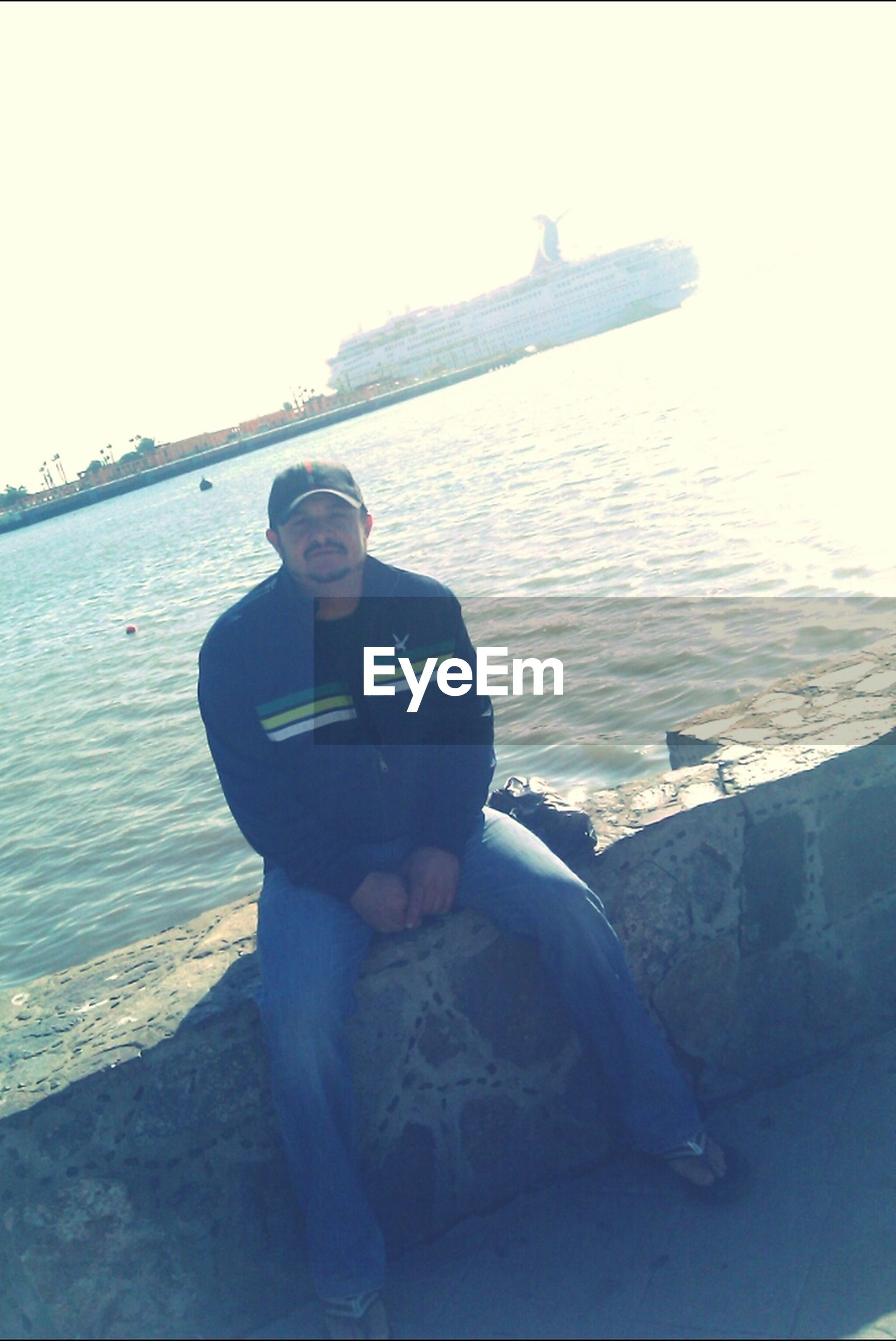 lifestyles, leisure activity, water, sea, young adult, young men, sitting, clear sky, person, casual clothing, vacations, full length, photography themes, rock - object, standing, sunglasses, relaxation, three quarter length