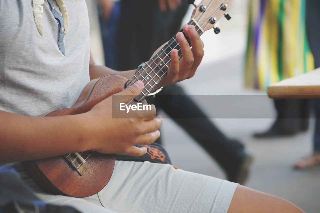 Midsection of man playing ukulele