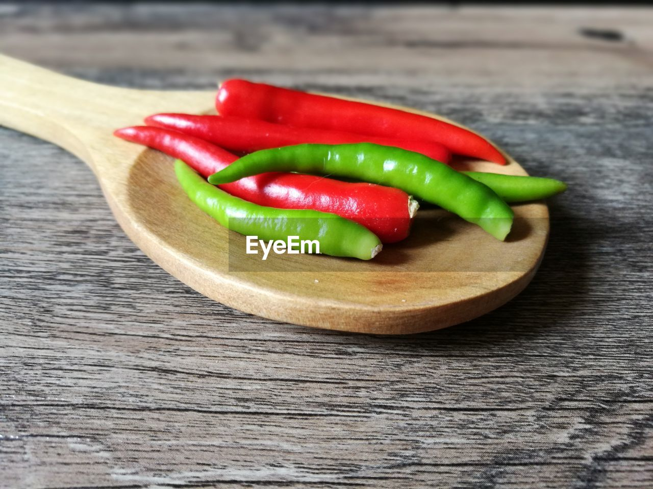 Close-up of chili peppers in wooden spoon on table