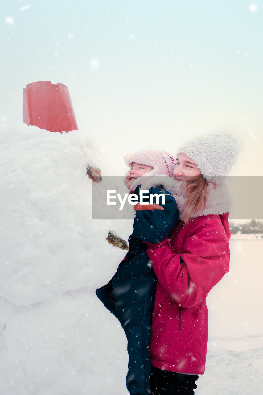 Teenage Girl Carrying Sister By Snowman Against Sky