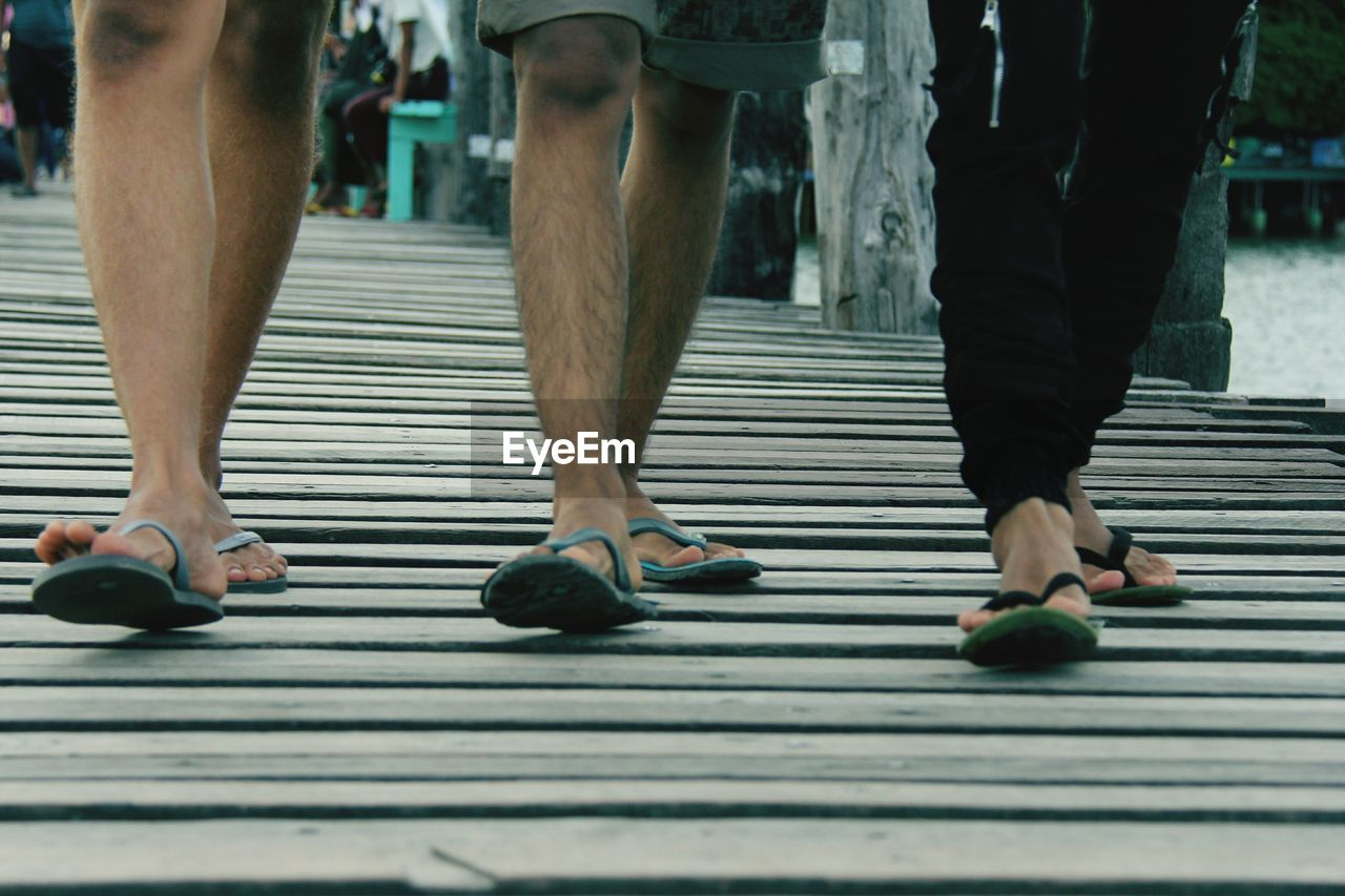 Low Section Of People Walking On Boardwalk