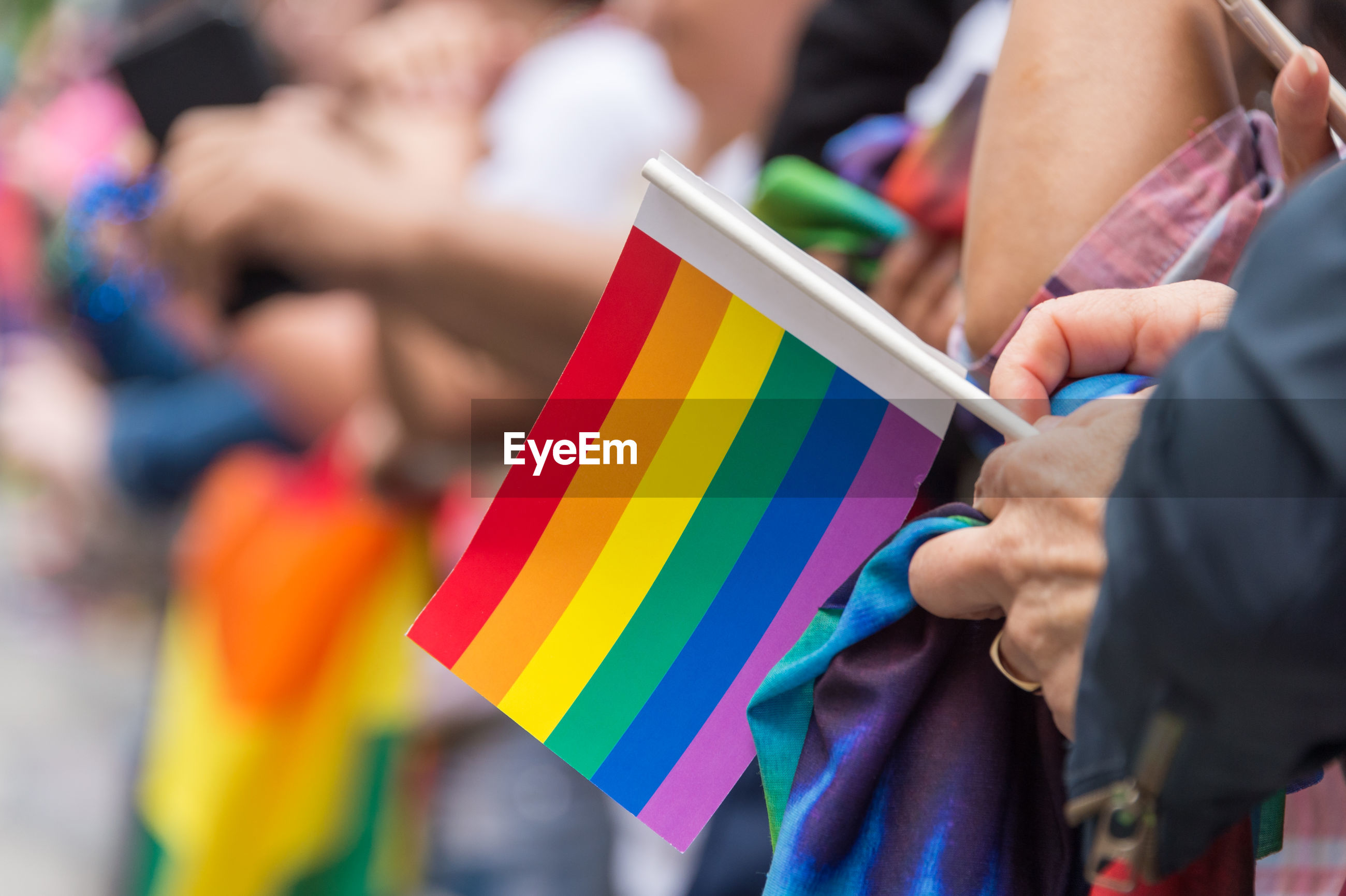 Close-up of hand holding rainbow flag