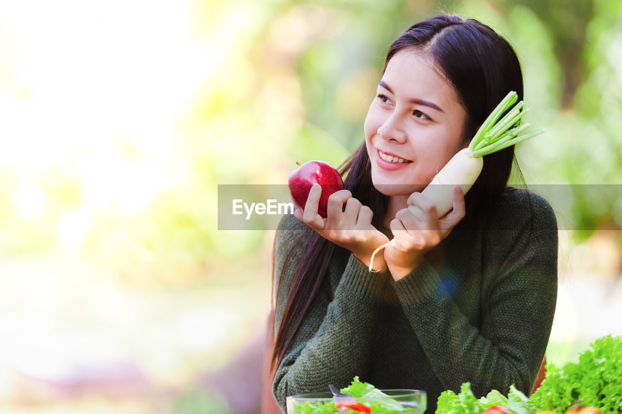 Smiling young woman with vegetables sitting outdoors