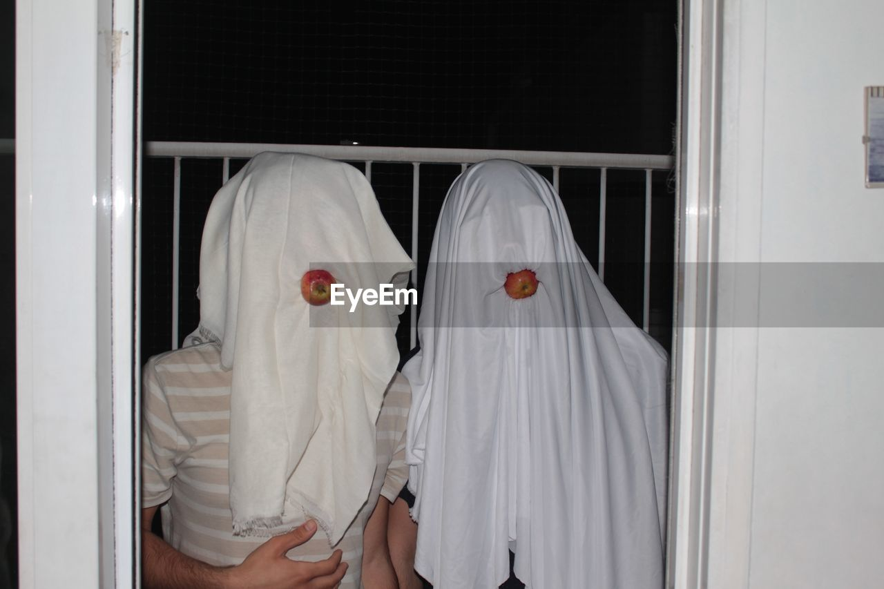 Male Friends Faces Covered With White Fabrics In Balcony At Night