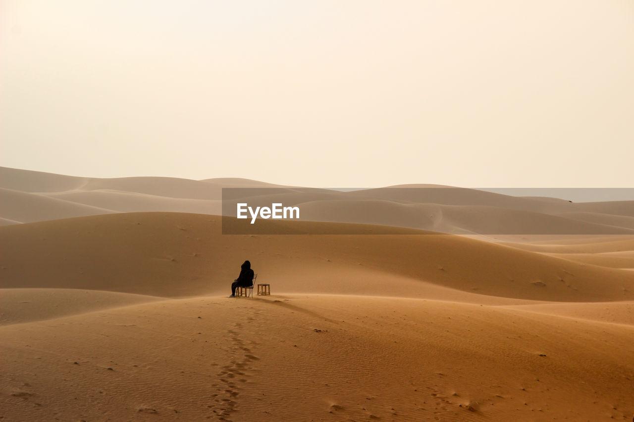 Full length of woman on sand dune in desert against sky