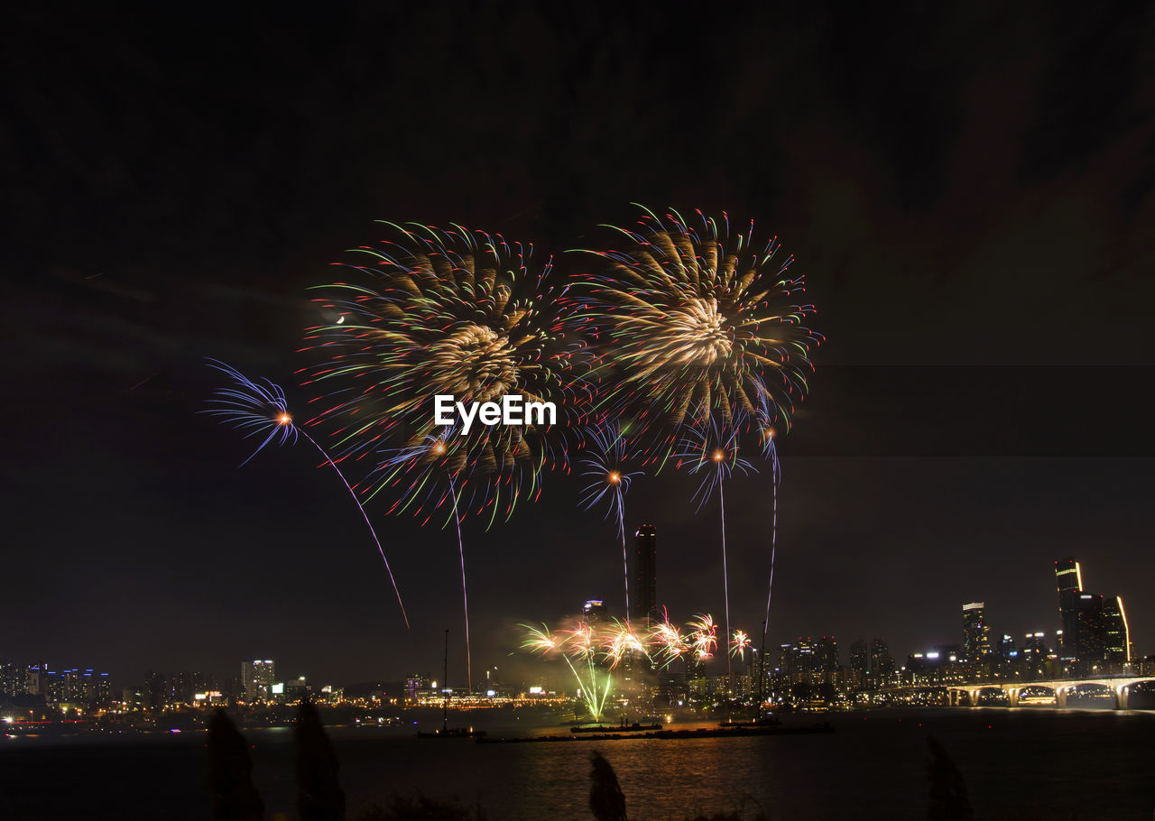 night, firework, illuminated, firework display, motion, exploding, architecture, building exterior, long exposure, event, firework - man made object, celebration, arts culture and entertainment, sky, glowing, built structure, nature, blurred motion, multi colored, city, sparks, light, cityscape, outdoors, no people, office building exterior, skyscraper