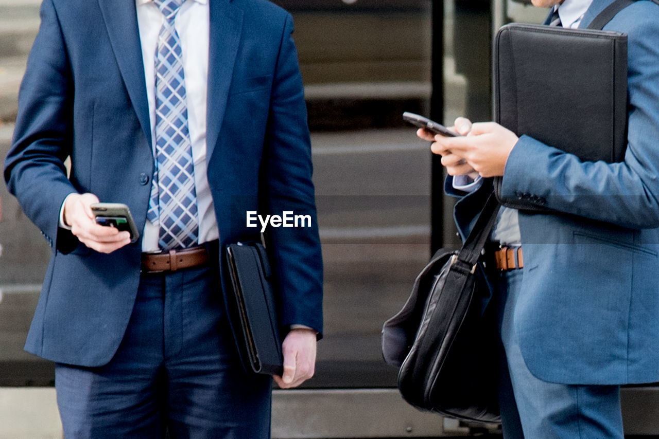Midsection of businessmen text messaging while standing outdoors