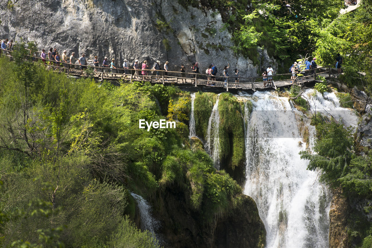 People walking on footbridge by waterfall