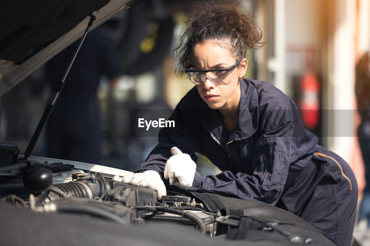 Mechanic repairing the motor or electric parts of a car in a garage