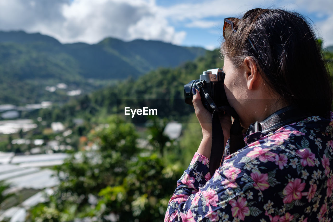 Side View Of Woman Photographing With Digital Camera On Mountain