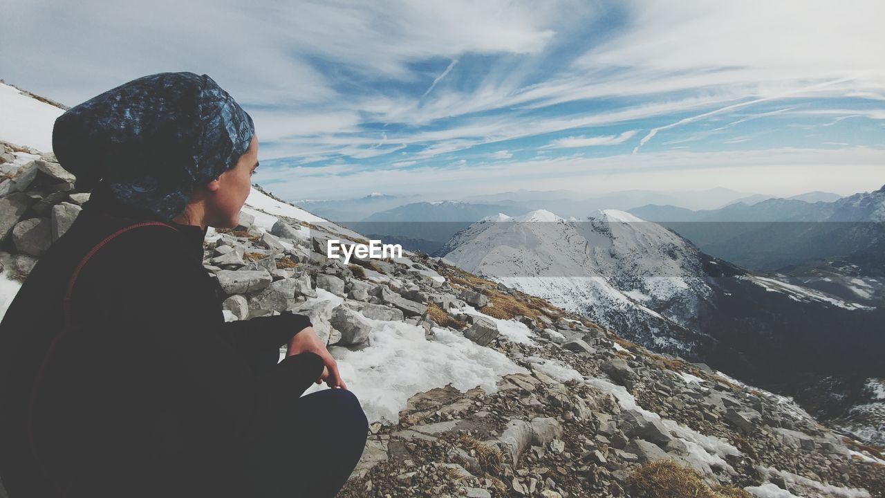 Side View Of Woman On Mountain Landscape Against Sky