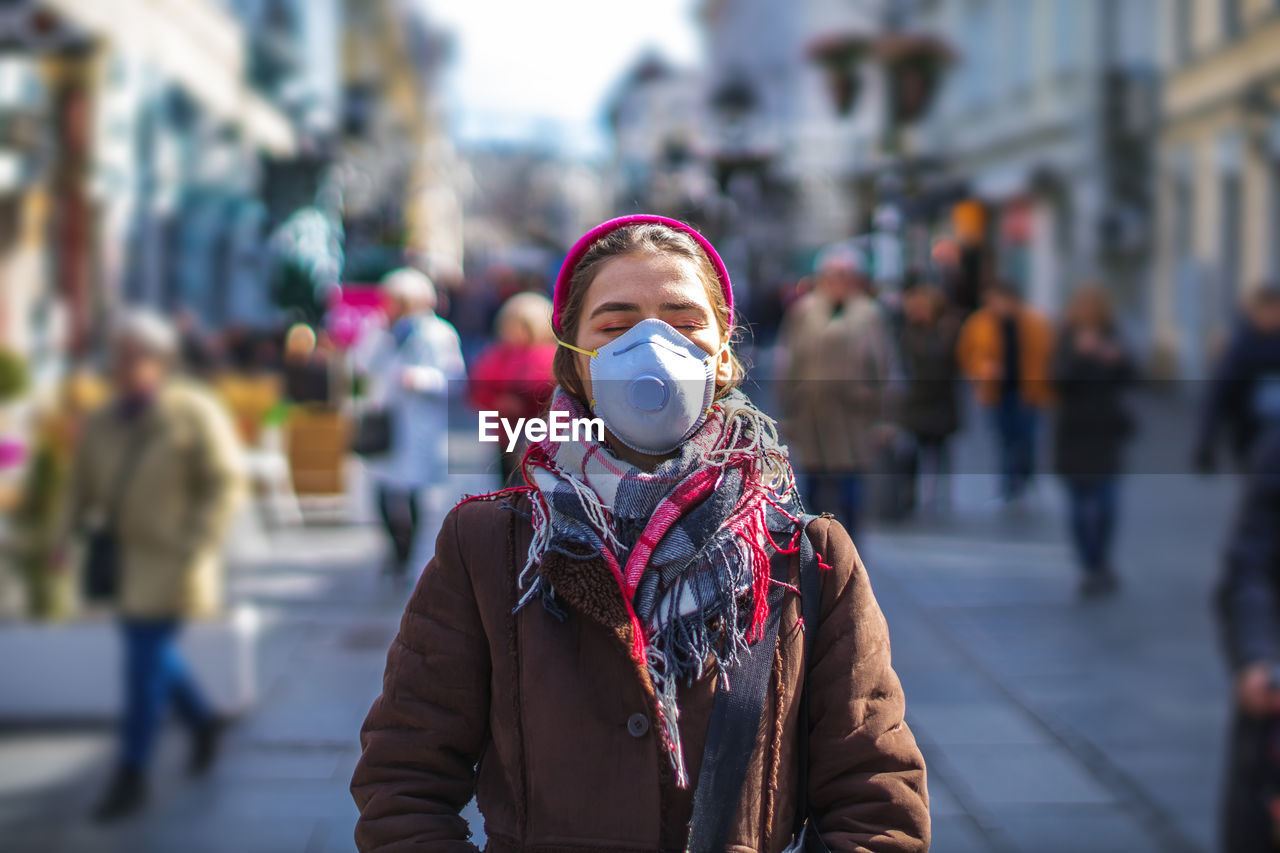 Woman wearing mask while standing in city