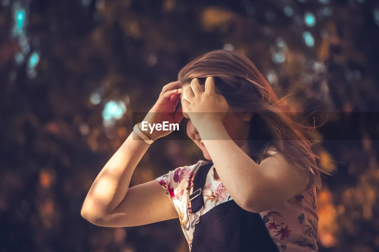 one person, real people, focus on foreground, hair, hairstyle, women, lifestyles, long hair, leisure activity, emotion, young women, young adult, adult, waist up, casual clothing, covering, headshot, hand, obscured face, beautiful woman