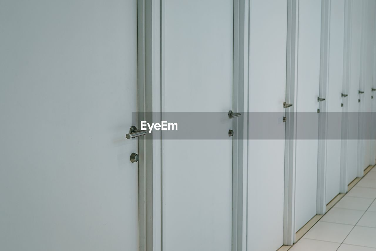 door, safety, protection, security, entrance, closed, no people, indoors, lock, metal, day, handle, white color, bathroom, dressing room, open, architecture, close-up, built structure, silver colored