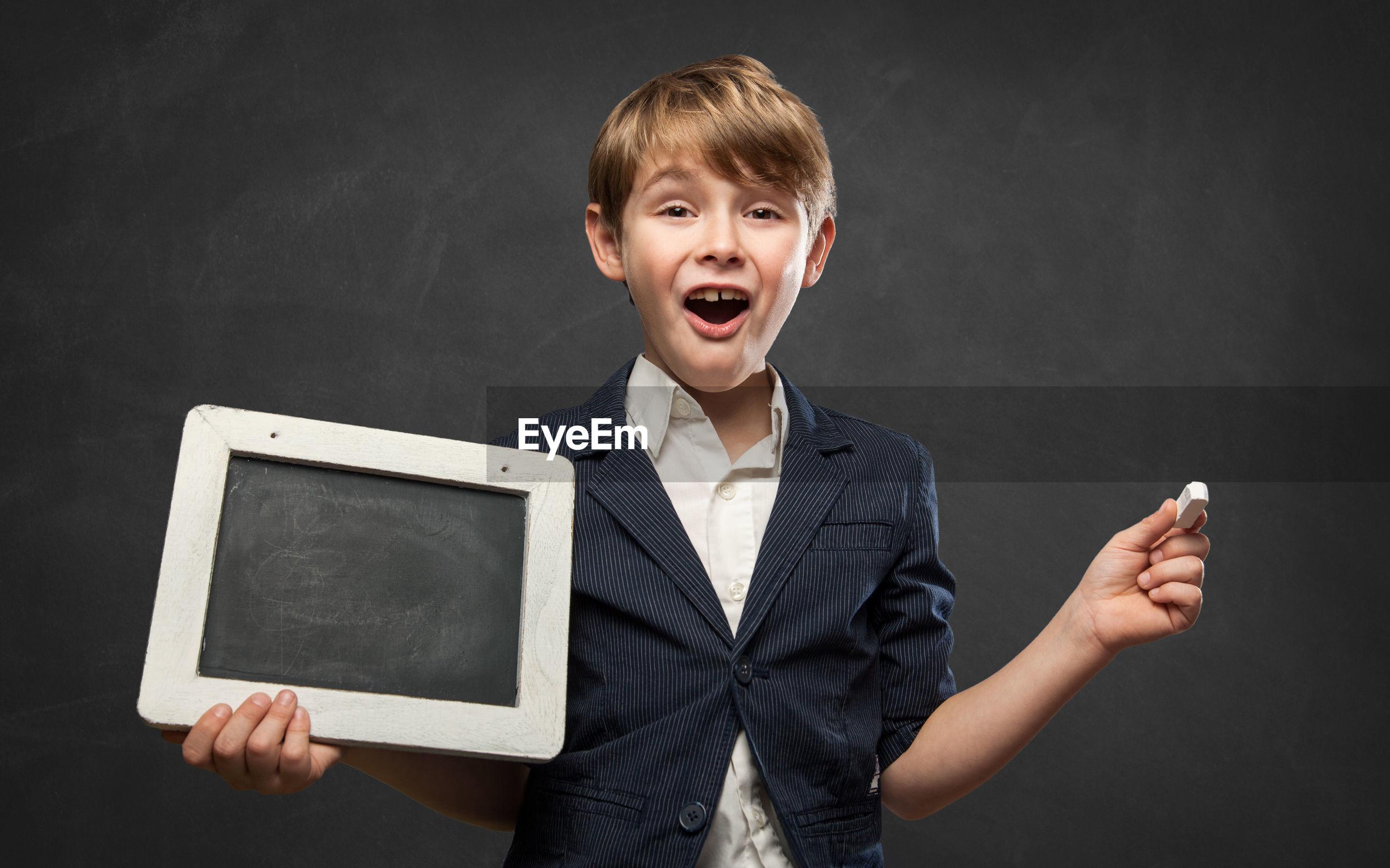 Portrait of boy holding slate standing against black background