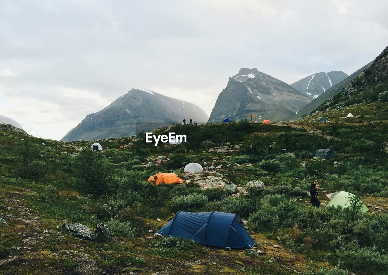 mountain, tent, environment, beauty in nature, camping, adventure, sky, landscape, scenery, nature, mountain range, mountain peak, hiking, land, scenics - nature, wilderness, travel, activity, grass, high