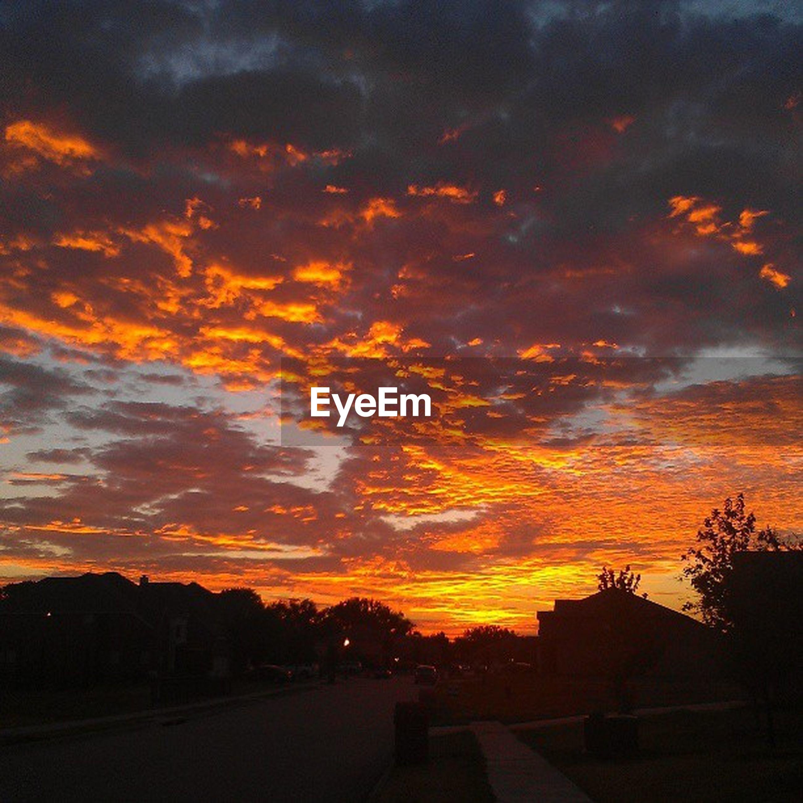 sunset, sky, orange color, cloud - sky, silhouette, dramatic sky, beauty in nature, scenics, cloudy, building exterior, cloud, built structure, tranquil scene, nature, tranquility, architecture, moody sky, road, idyllic, landscape