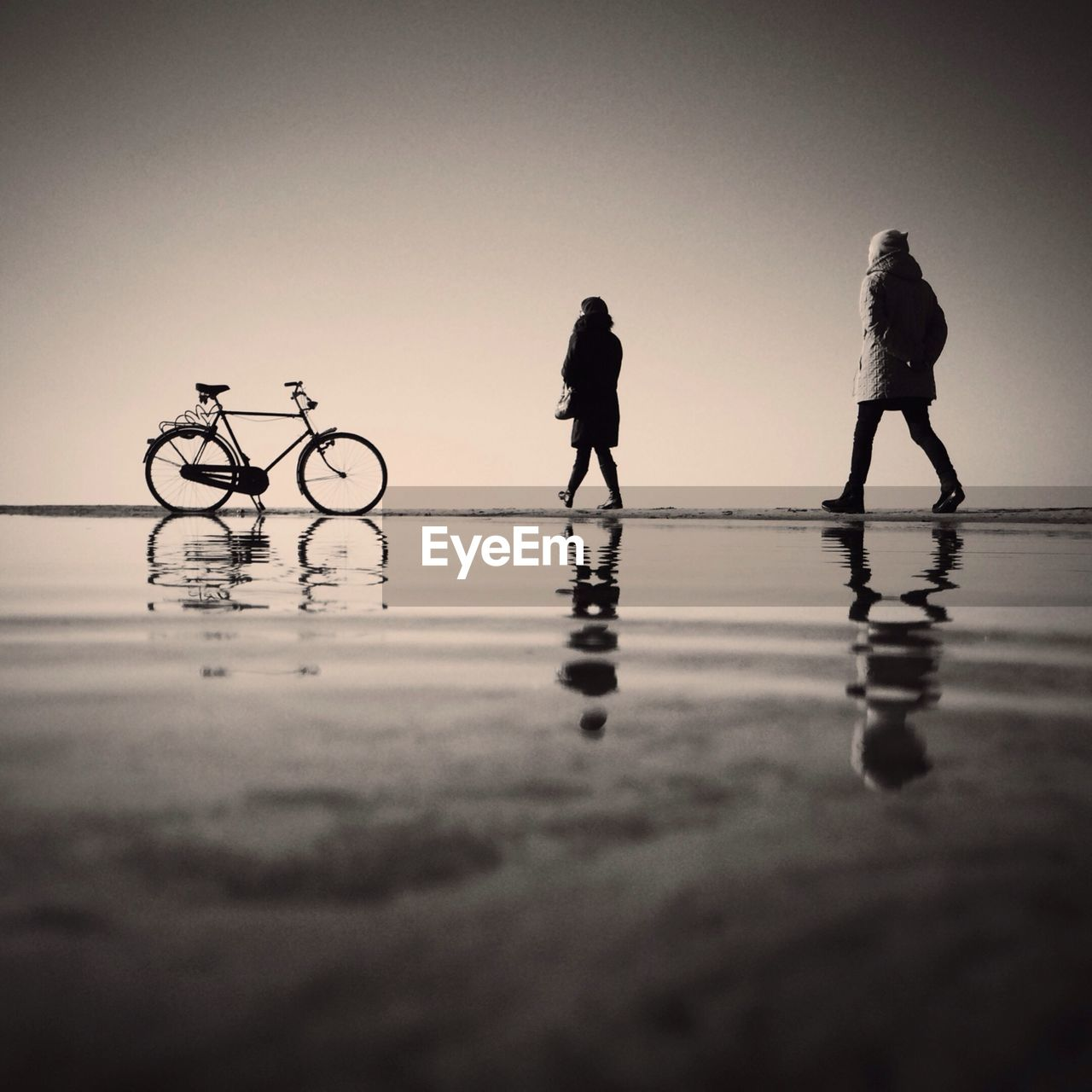Low angle view of two people and bicycle on beach