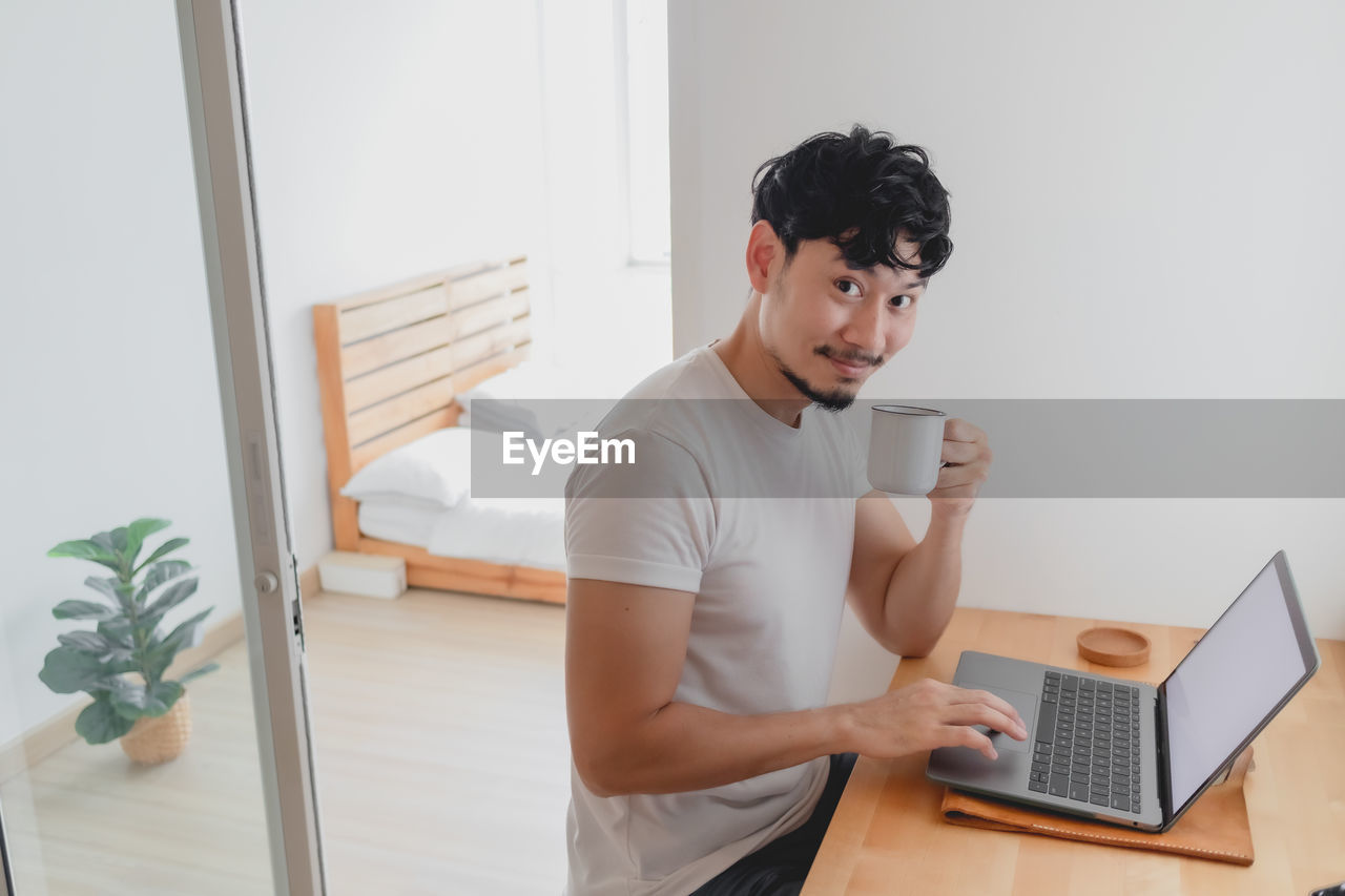 YOUNG MAN USING PHONE WHILE SITTING AT HOME