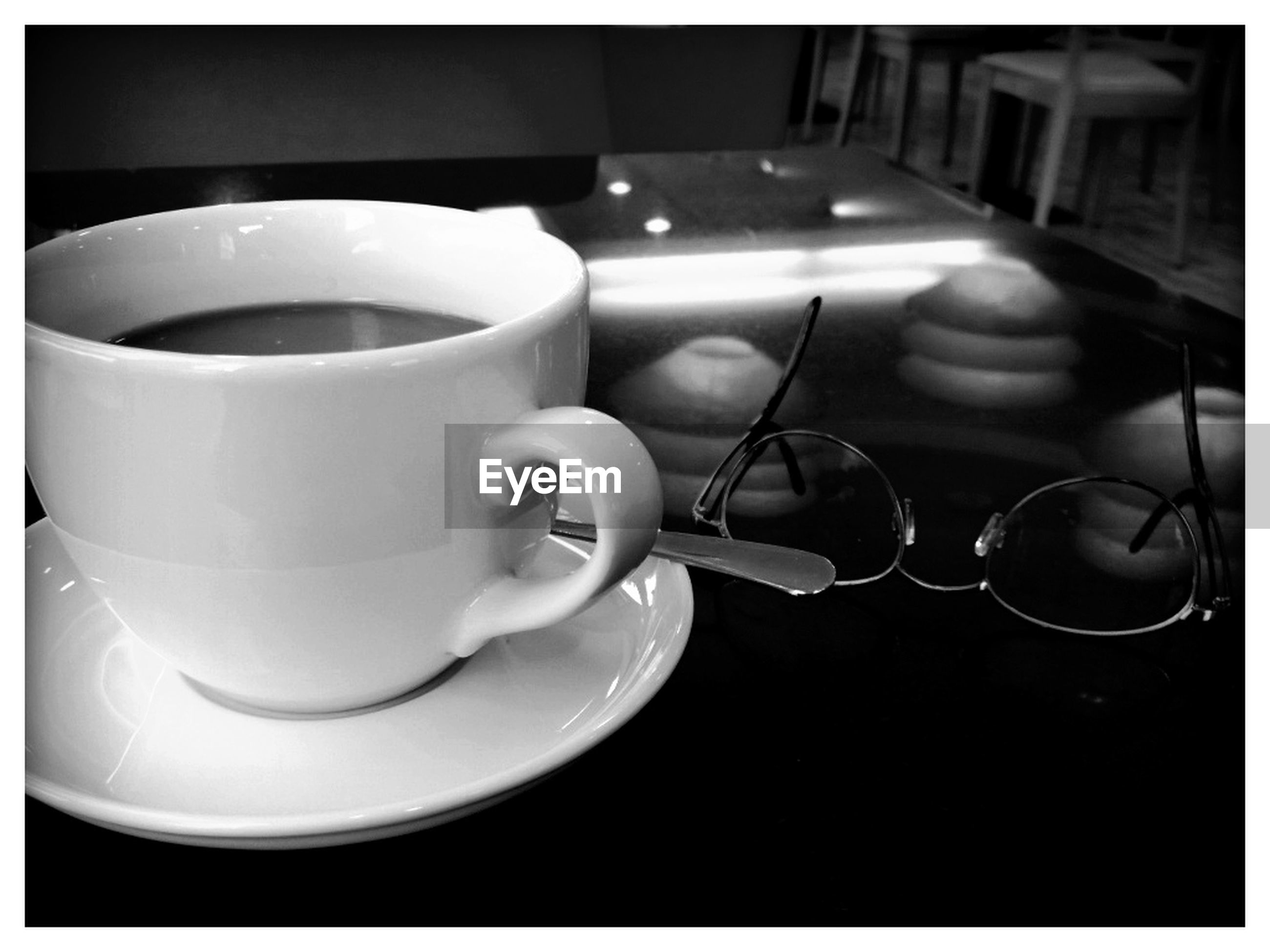 Close-up of coffee and eyeglasses on table