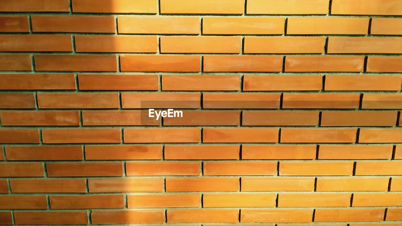 FULL FRAME SHOT OF YELLOW BRICK WALL IN ROW
