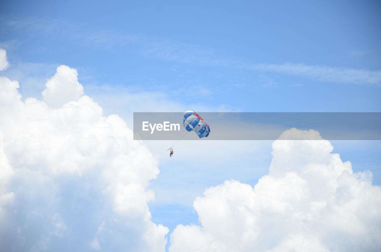 People Paragliding Against Cloudy Sky