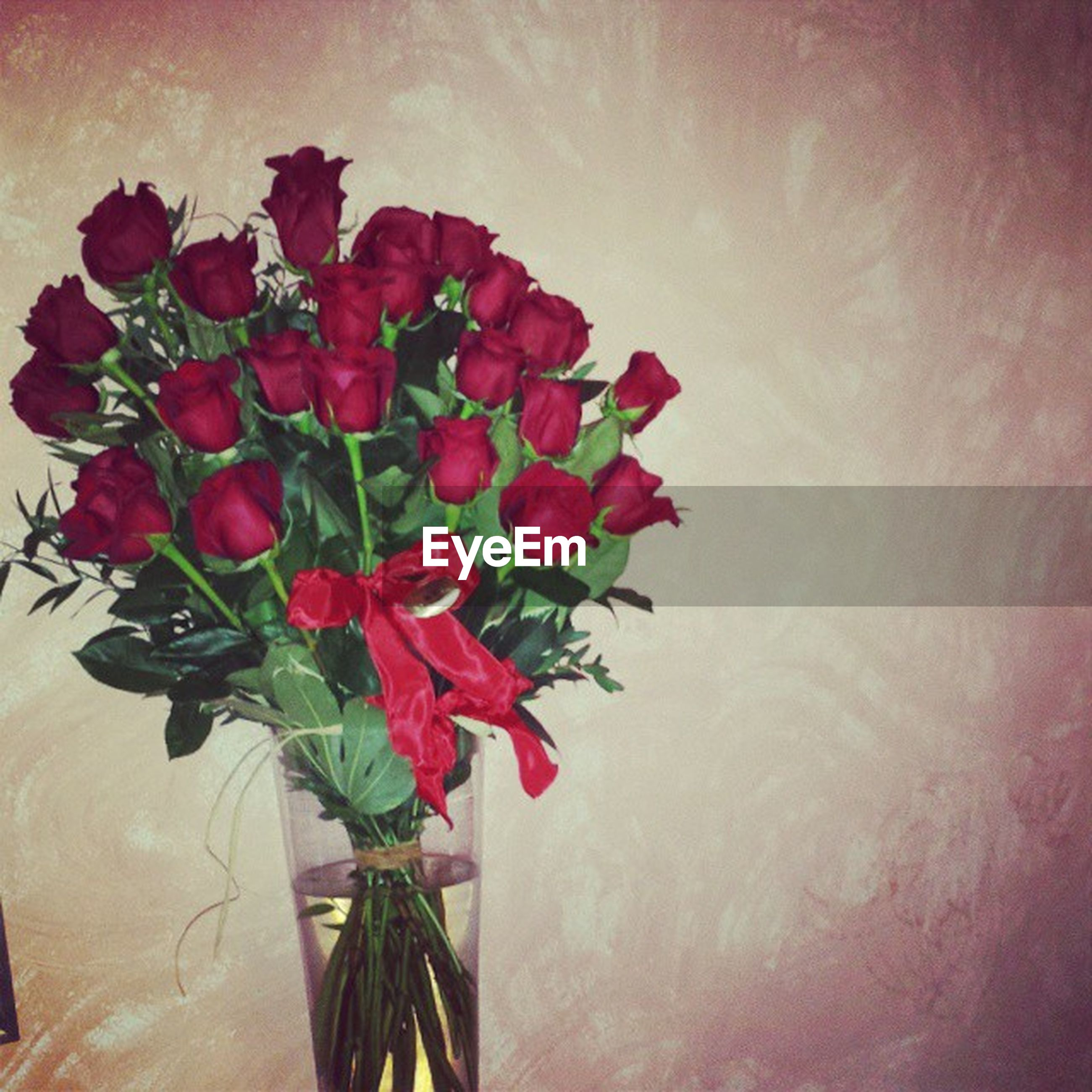 flower, freshness, indoors, petal, fragility, red, beauty in nature, flower head, wall - building feature, vase, plant, nature, growth, rose - flower, decoration, table, close-up, bunch of flowers, bouquet, stem