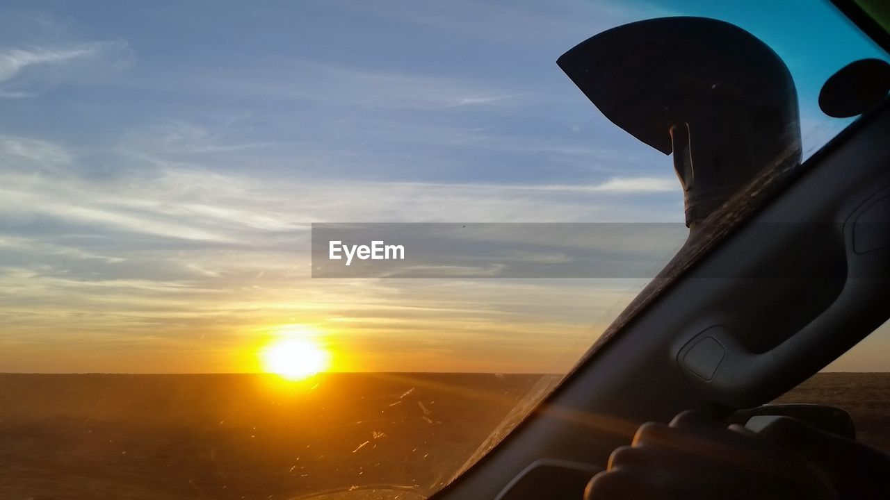 transportation, sky, vehicle interior, sunset, mode of transport, cloud - sky, journey, travel, sun, beauty in nature, nature, one person, scenics, land vehicle, real people, outdoors, close-up, airplane, sea, day, people