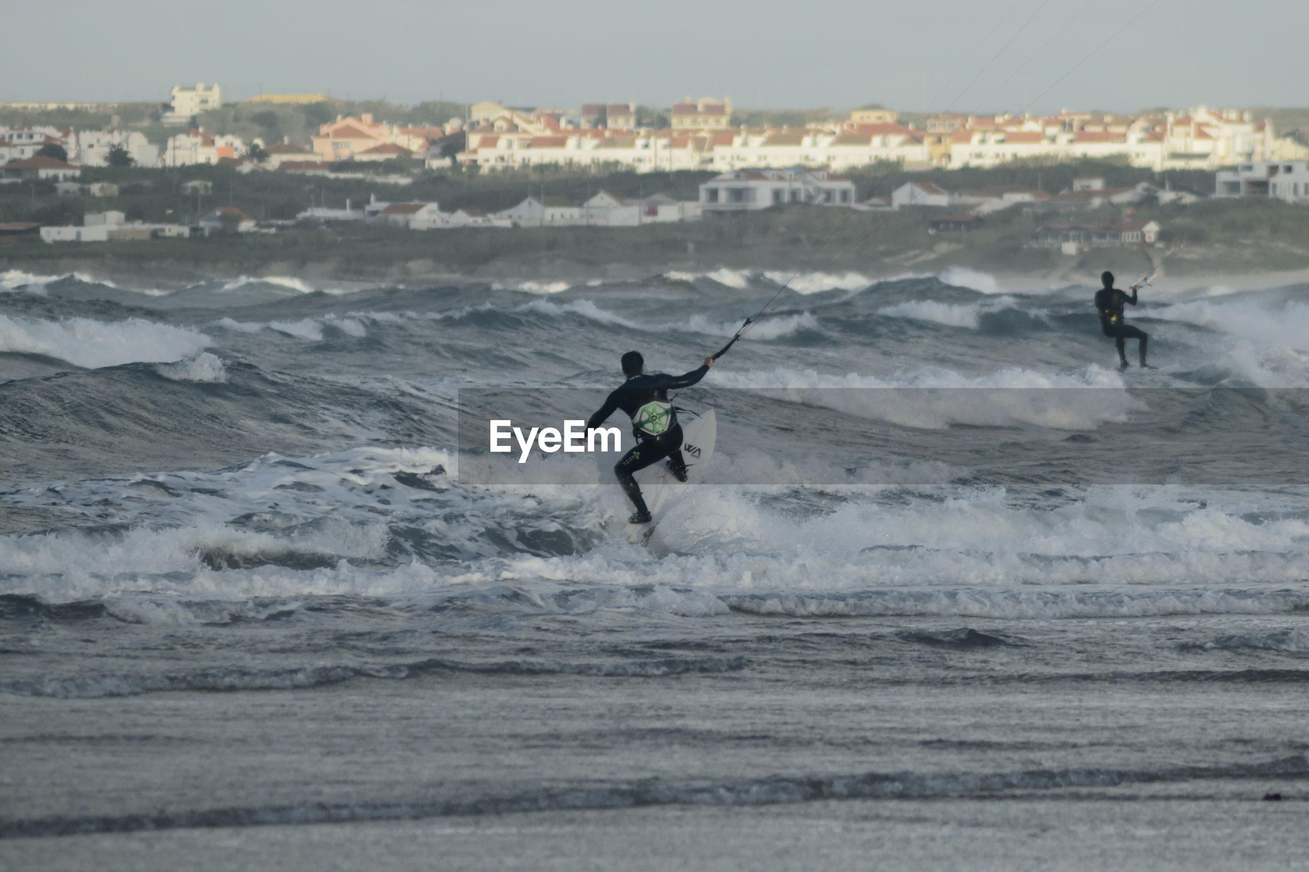 Men surfing in sea against sky