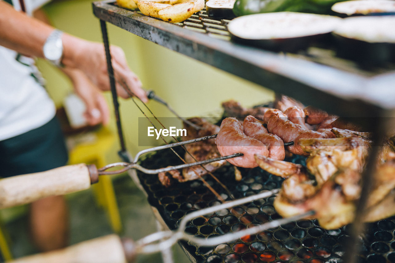 Midsection Of Man Preparing Meat On Barbecue Grill