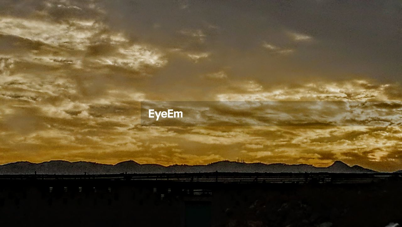 sky, sunset, cloud - sky, mountain, beauty in nature, silhouette, water, scenics - nature, nature, architecture, tranquil scene, no people, tranquility, mountain range, outdoors, built structure, dusk, building exterior, dramatic sky