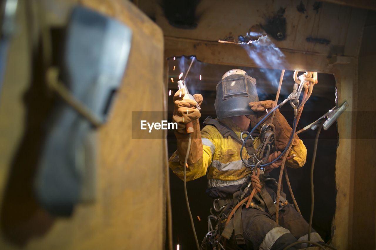 occupation, protective workwear, working, one person, men, helmet, real people, headwear, protection, industry, safety, hat, skill, holding, standing, expertise, indoors, fuel and power generation