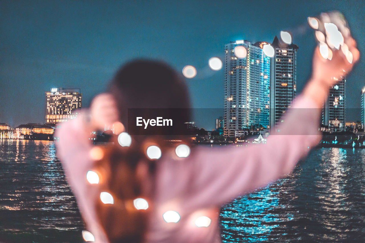 REAR VIEW OF PERSON PHOTOGRAPHING ILLUMINATED CITYSCAPE AGAINST SKY