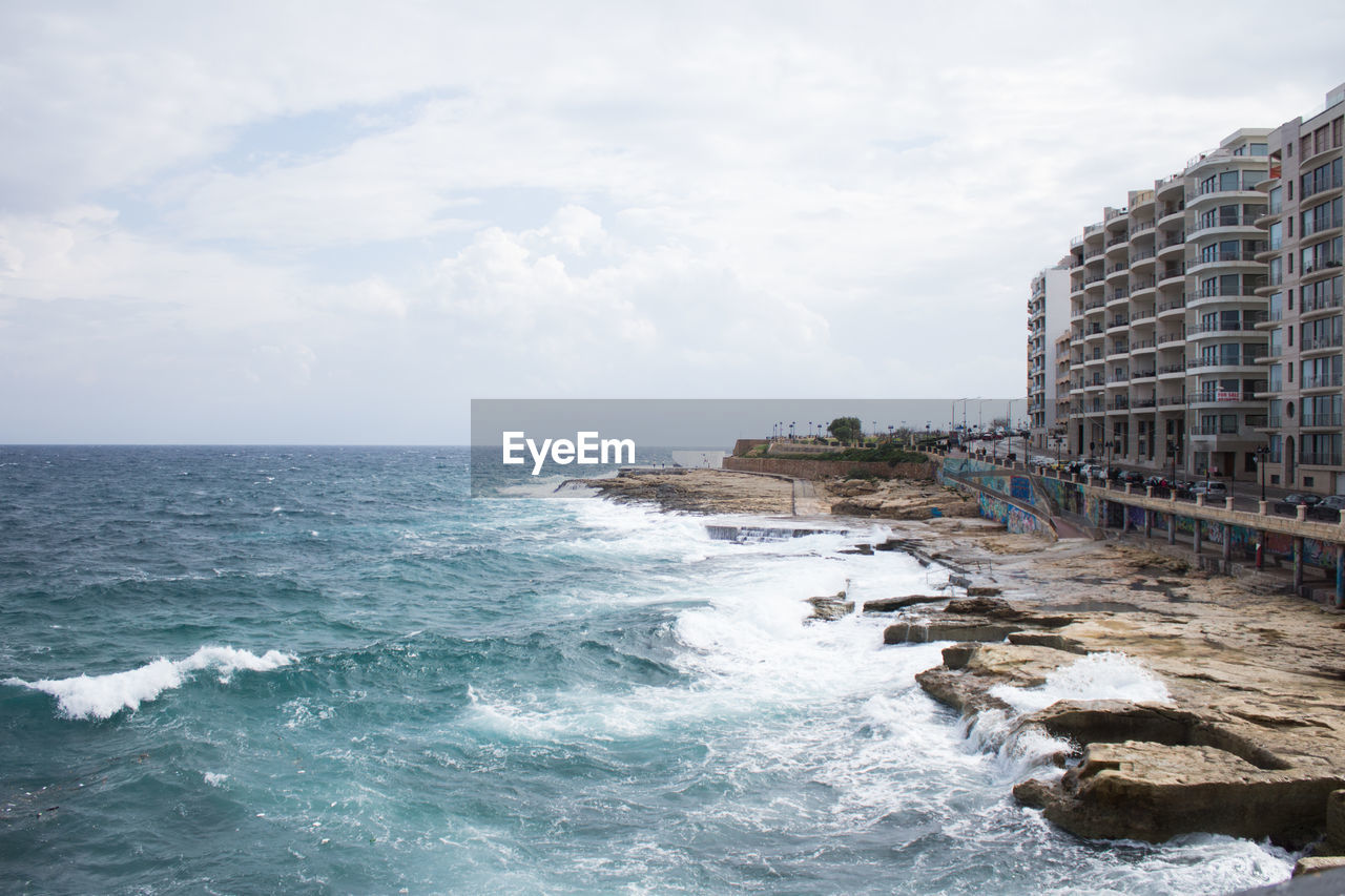 sea, water, sky, building exterior, cloud - sky, architecture, built structure, motion, wave, nature, scenics - nature, horizon, aquatic sport, horizon over water, sport, building, beauty in nature, waterfront, rock, no people, outdoors, power in nature, breaking