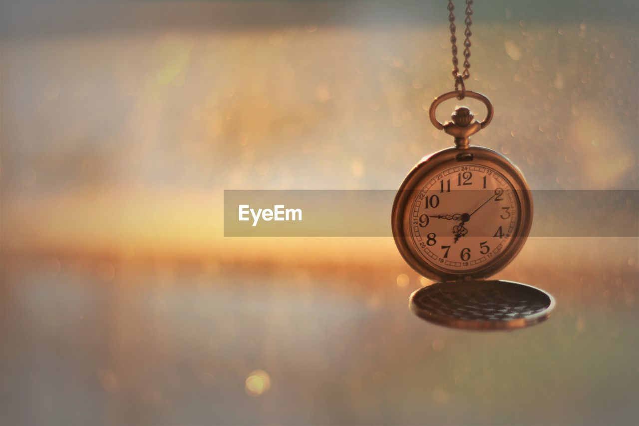 Close-up of pocket watch hanging against blurred background