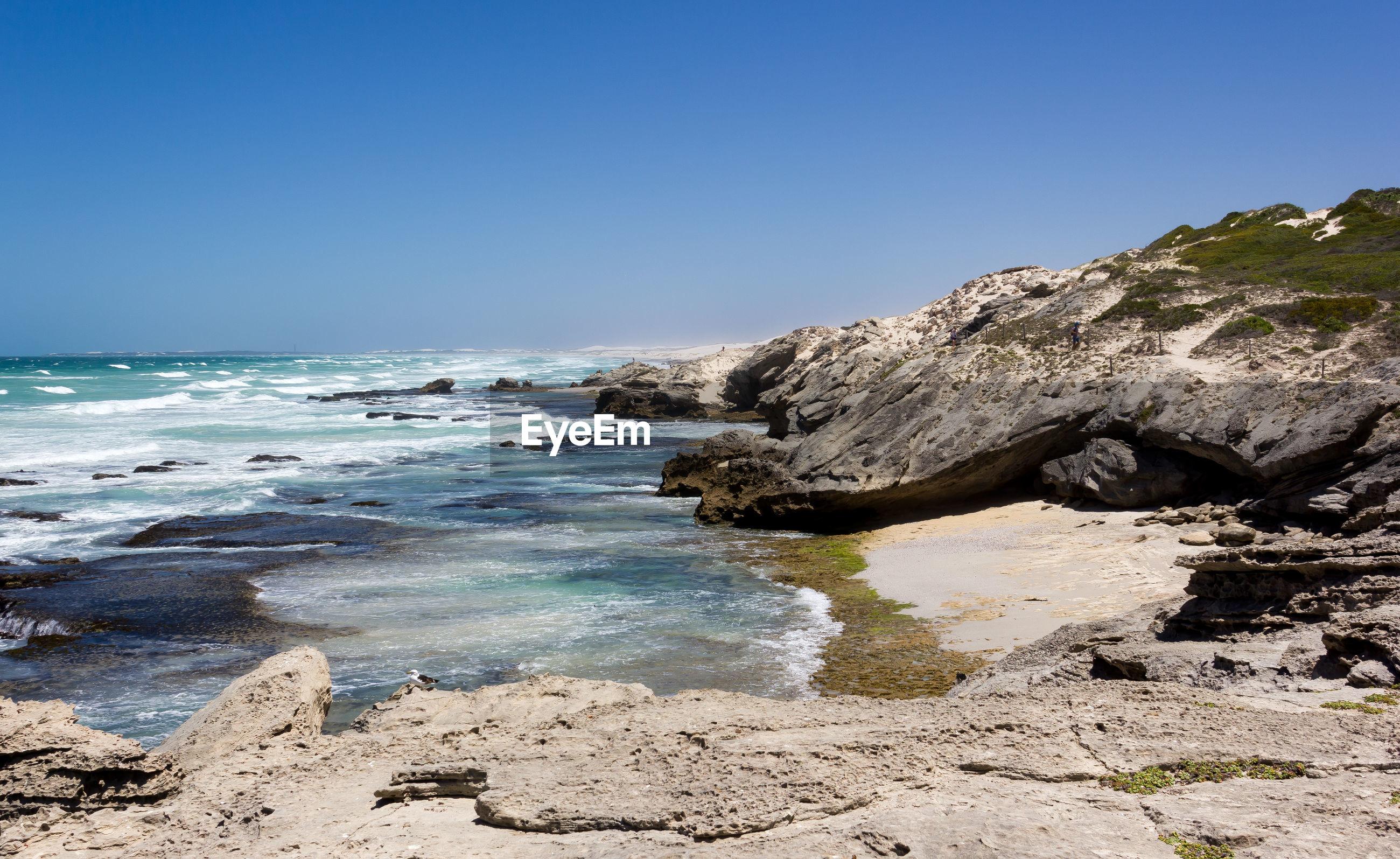 ROCKS ON SEA AGAINST CLEAR BLUE SKY
