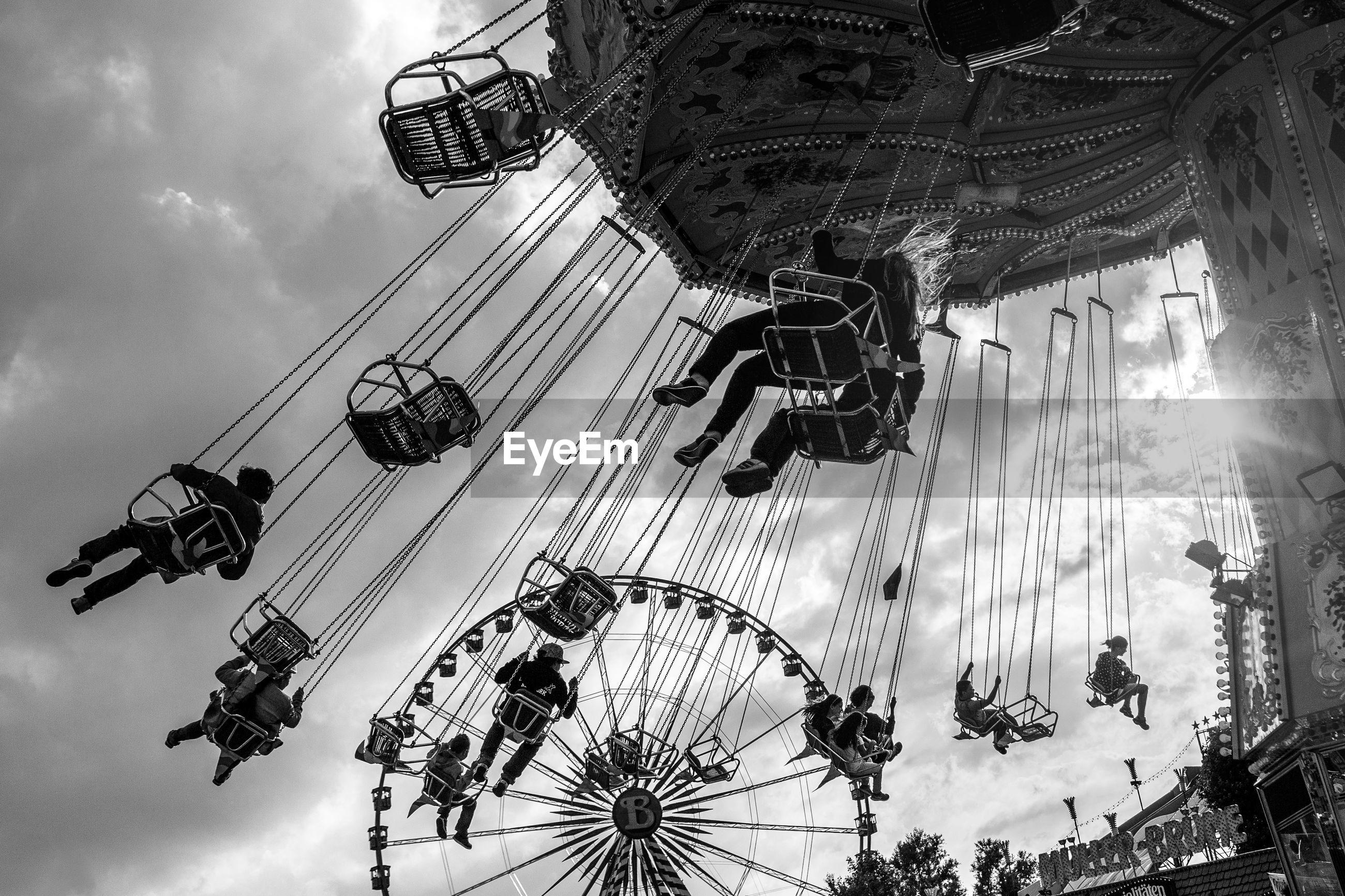 low angle view, sky, architecture, built structure, building exterior, tree, cloud - sky, tall - high, amusement park, arts culture and entertainment, ferris wheel, amusement park ride, outdoors, cloudy, cloud, dusk, tower, no people, city, silhouette