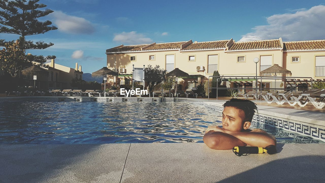 MAN RELAXING ON SWIMMING POOL AGAINST CITYSCAPE