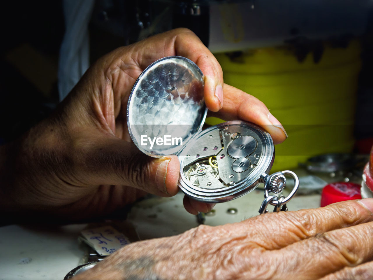 Cropped Hands Of Man Repairing Pocket Watch On Table